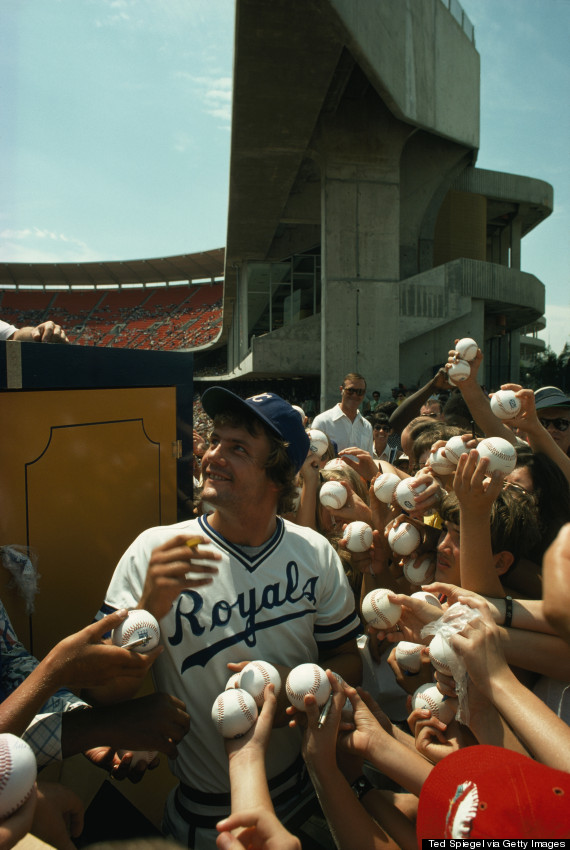 Young fans hold up baseballs for Royals star George Brett to sign